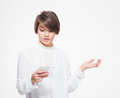 Amazed female holding copyspace on palm and using mobile phone pretty young in white blouse over white background Stock Photo