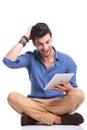 Amazed ha messo le buone notizie a sedere casuali della lettura dell uomo sulla compressa Fotografia Stock Libera da Diritti