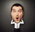 Amazed man with big head funny picture of over dark background Stock Photography