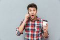 Amazed man holding takeaway coffee and talking on mobile phone Royalty Free Stock Photo