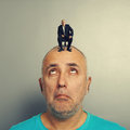 Amazed man looking up at calm businessman on his head Royalty Free Stock Images