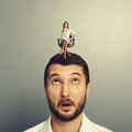 Amazed man with small angry woman men women on the head over grey background Royalty Free Stock Photo