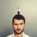 Amazed man with small unhappy man on the head Royalty Free Stock Photo