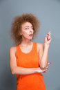 Amazed pretty woman pointing away on copyspace shocked young curly in orange top Stock Photo