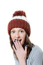 Amazed pretty young girl in winter knitted hat isolated closeup picture of with her hand over her mouth Stock Images