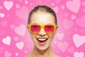 Amazed teen girl in sunglasses love happiness and valentines day concept pink on background with hearts Royalty Free Stock Photography