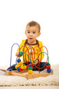 Amazed toddler with wooden toy boy sitting on carpet and playing Royalty Free Stock Photography