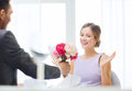 Amazed woman recieving bouquet of flowers restaurant couple and holiday concept women from husband or boyfriend at restaurant Stock Photo