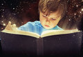 Amazed young boy with magic book Stock Photography