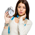 Amazed young girl with alarm clock wearing colored scarf and beige pullover isolated on white Stock Photo