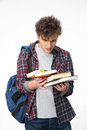 Amazed young man with books over gray background Stock Photos