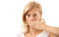 Amazed young woman covering mouth on white over background Stock Image