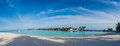 Amazing beautiful tropical beach panorama of water bungalos  near the ocean with palm trees under the blue sky at Maldives Royalty Free Stock Photo