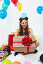 Amazing girl showing present box with red bow, smiling happily