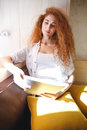 Amazing redhead young lady in cafe reading magazine. Royalty Free Stock Photo