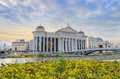 Amazing sunrise of archaeological museum in skopje macedonia with river vardar bright colorful sky and spring flowers foregroung Royalty Free Stock Photo