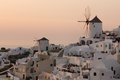 Amazing Sunset over white windmills in  town of Oia and panorama to Santorini island, Thira, Greece Royalty Free Stock Photo