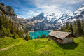 Amazing tourquise Oeschinnensee with waterfalls, wooden chalet and Swiss Alps in Berner Oberland Royalty Free Stock Photo