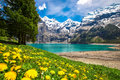 Amazing tourquise Oeschinnensee with waterfalls, wooden chalet and Swiss Alps, Berner Oberland, Switzerland Royalty Free Stock Photo