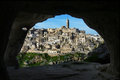 An amazing view from inside a cave looking at the dwelling village of sassi di matera through another prehistoric dwelling across Royalty Free Stock Images