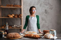 Amazing young lady baker standing at bakery near bread Royalty Free Stock Photo