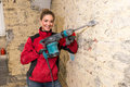 Ambitious craftswoman with caulking hammer in front of brick wal Royalty Free Stock Photo