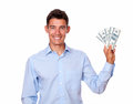 Ambitious man smiling and holding cash dollars a portrait of an on blue shirt while looking at you on isolated background Royalty Free Stock Image