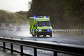 Ambulance british responding to an emergency in hazardous bad weather driving conditions on a uk motorway Royalty Free Stock Photo