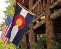 America and colorado flags the of flying side by side outside a log cabin Stock Photography