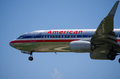 American airlines plane in flight closeup as it is coming for a landing with it s wheels down Royalty Free Stock Image