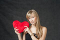 American blond haired woman with a heart shaped long female holding in hands red cushion on dark background Stock Images