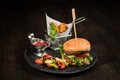 American burger on black plate, chips, salad, sauce Royalty Free Stock Photo