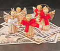 American business angels with ribbons and wings on top of united states dollar bills representing funding new businesses Stock Photography