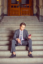 American Businessman texting on cell phone, sitting on stairs Royalty Free Stock Photo