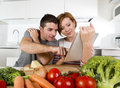 American couple in domestic kitchen wife following recipe in digital pad working together with husband young happy her Royalty Free Stock Images