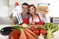 American couple in stress at home kitchen in cooking apron asking for help frustrated