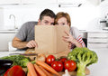 American couple working in domestic kitchen following recipe reading cookbook together young happy with carrots tomatoes and Stock Photography