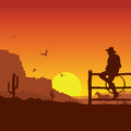 American Cowboy on wild west sunset landscape in the evening Royalty Free Stock Photo