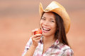 American cowgirl eating peach smiling happy or nectarine fruit and laughing wearing cowboy hat outside healthy concept with Stock Image