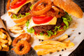 American cuisine with cheesburger onion rings and french fries selective focus on the cheeseburger Stock Photography