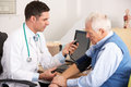 American doctor taking senior man's blood pressure Royalty Free Stock Photo