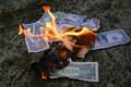 American dollars burning on the pavement with flames in the centre Royalty Free Stock Photos