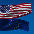 American and european union flags waving upon blue sky Stock Photography