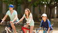 American family riding bicycles in park togetherness on sunny day Stock Images