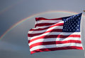 American flag against a cloudy sky with a rainbow waving Royalty Free Stock Images