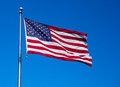 American flag blue sky flying in a breeze against a clear background Stock Photography
