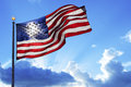 American flag fluttering in the wind under a cloudy sky Stock Photos