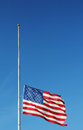 American flag flying at half staff in memory of Newtown massacre victims . Royalty Free Stock Photo