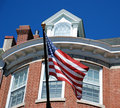 American Flag in Front of Brick Home Stock Photo