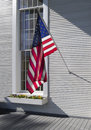 American flag hanging in front of a colonial window frame Stock Photos